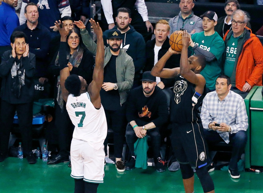 Milwaukee Bucks' Khris Middleton shoots a three-point basket over Boston Celtics' Jaylen Brown (7) with less than a second to play in the fourth quart