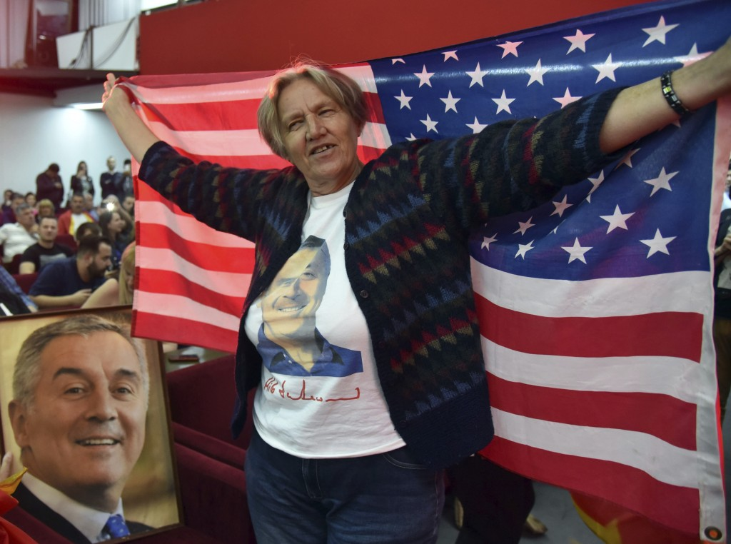 A supporter of Montenegro's former prime minister and long-ruling Democratic Party of Socialists leader Milo Djukanovic holds an American flag during
