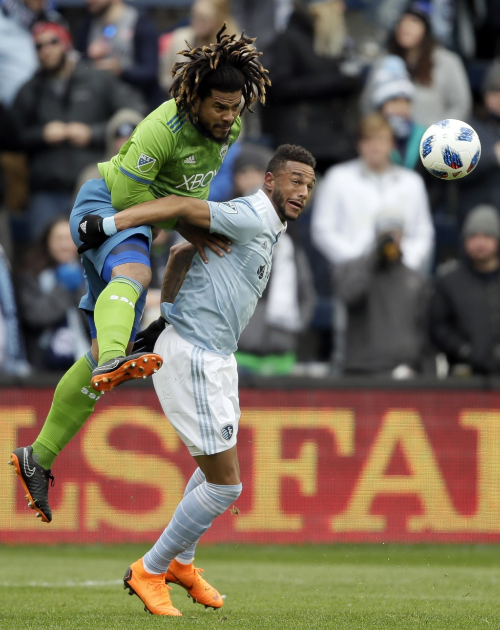 Seattle Sounders defender Roman Torres, left, heads the ball over Sporting Kansas City forward Khiry Shelton, right, during the first half of an MLS s