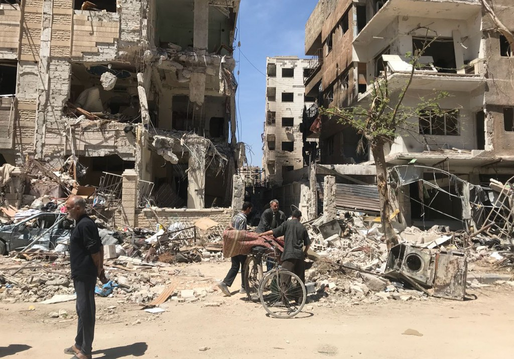 People stand in front of damaged buildings, in the town of Douma, the site of a suspected chemical weapons attack, near Damascus, Syria, Monday, April