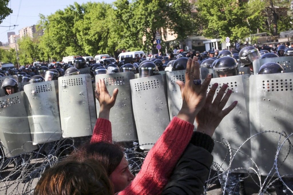 Police officers block the way for opposition demonstrators as they march to protest the former president's shift into the prime minister's seat, in Ye