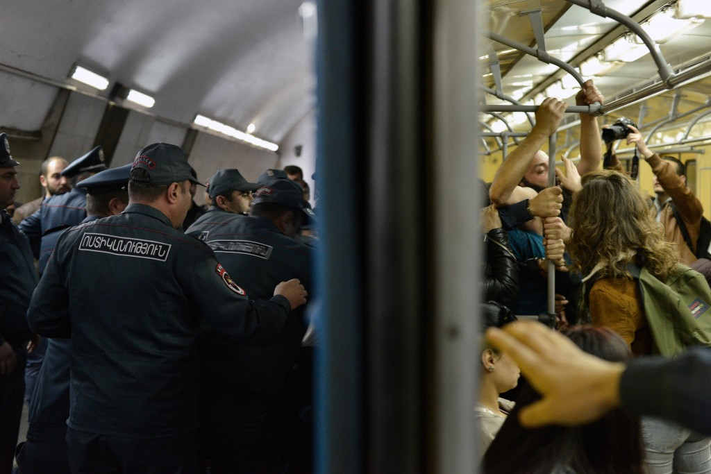 Opposition demonstrators block the entrance of an underground carriage during a protest against the former president's shift into the prime minister's