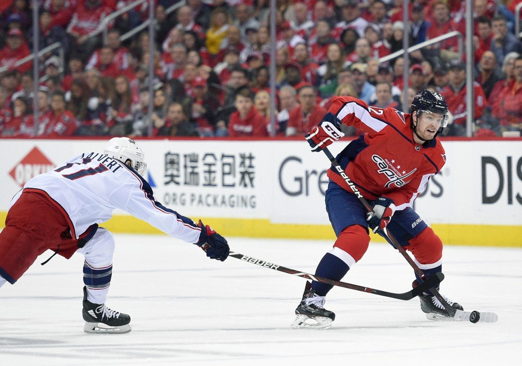 Washington Capitals center Evgeny Kuznetsov (92), of Russia, skates with the puck against Columbus Blue Jackets left wing Matt Calvert (11) during the