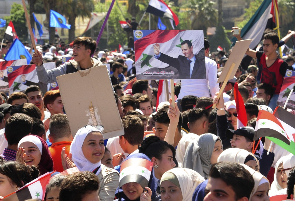 In this photo released by the Syrian official news agency SANA, protesters wave flags and a portrait of President Bashar Assad, as they march during a