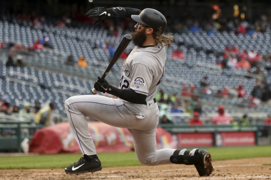 Colorado Rockies' Charlie Blackmon falls over while dodging a pitch during the eighth inning of a baseball game against the Washington Nationals at Na