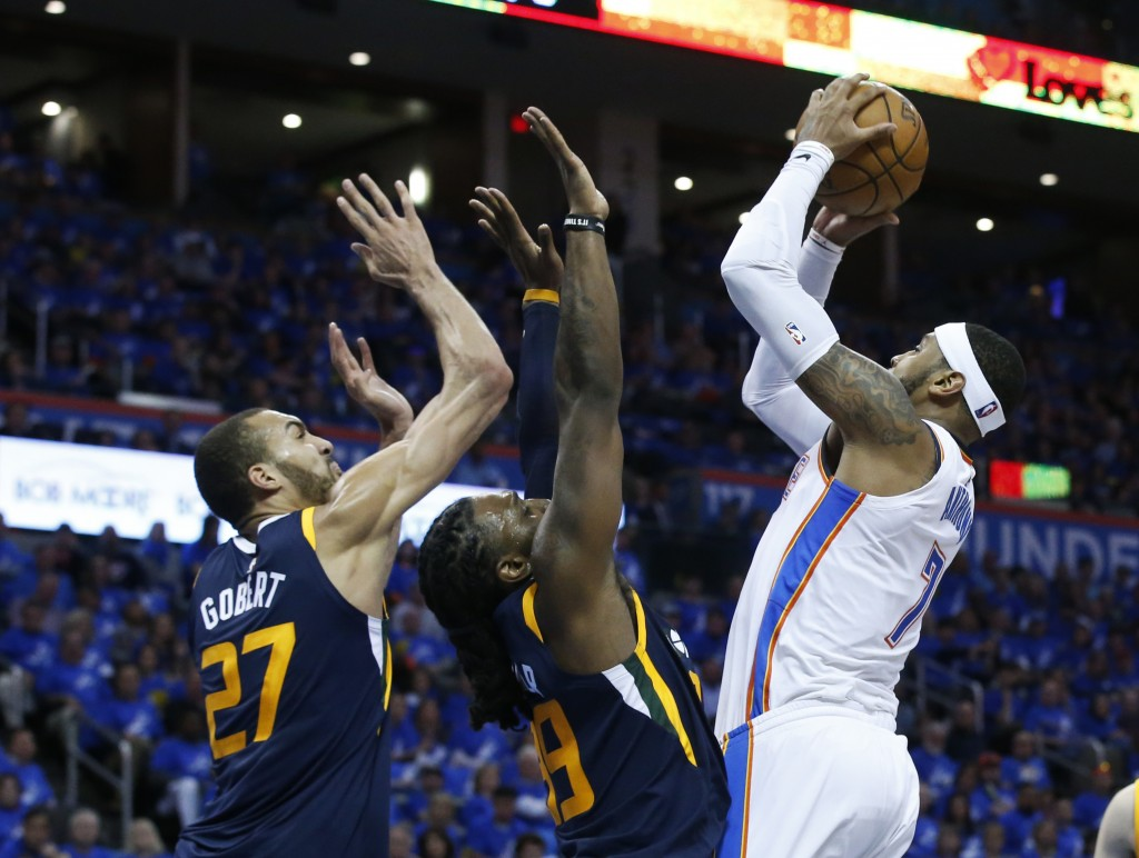 Oklahoma City Thunder forward Carmelo Anthony, right, goes up for a shot as Utah Jazz center Rudy Gobert (27) and forward Jae Crowder (99)stad defend