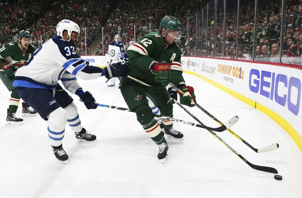 Minnesota Wild center Eric Staal (12) controls the puck in front of Winnipeg Jets defenseman Dustin Byfuglien (33) in the first period of an NHL hocke