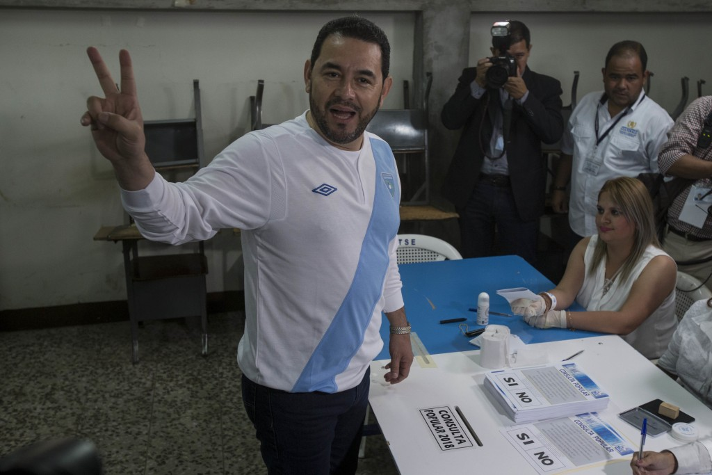 Guatemalan President Jimmy Morales poses for photographers before voting in a plebiscite concerning a border dispute with Belize, in Guatemala City, S