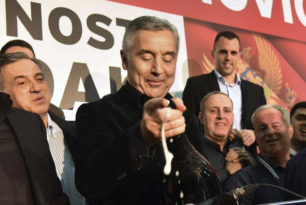 Montenegro's former prime minister and long-ruling Democratic Party of Socialists leader Milo Djukanovic opens a bottle of champagne during a celebrat