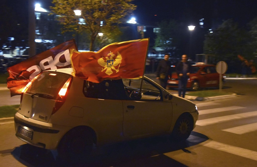 Supporters of Montenegro's former prime minister and long-ruling Democratic Party of Socialists leader Milo Djukanovic hold Montenegro and party flags