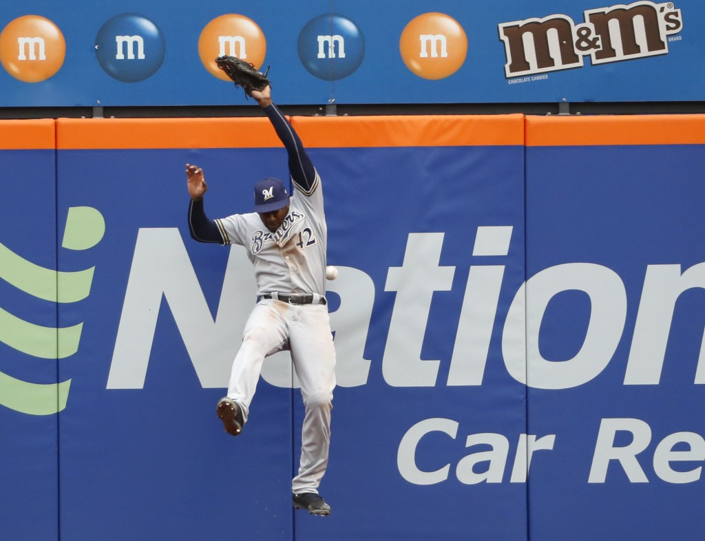 Milwaukee Brewers center fielder Lorenzo Cain (6) leaps but can't get Brandon Nimmo's fourth-inning triple in a baseball game against the New York Met