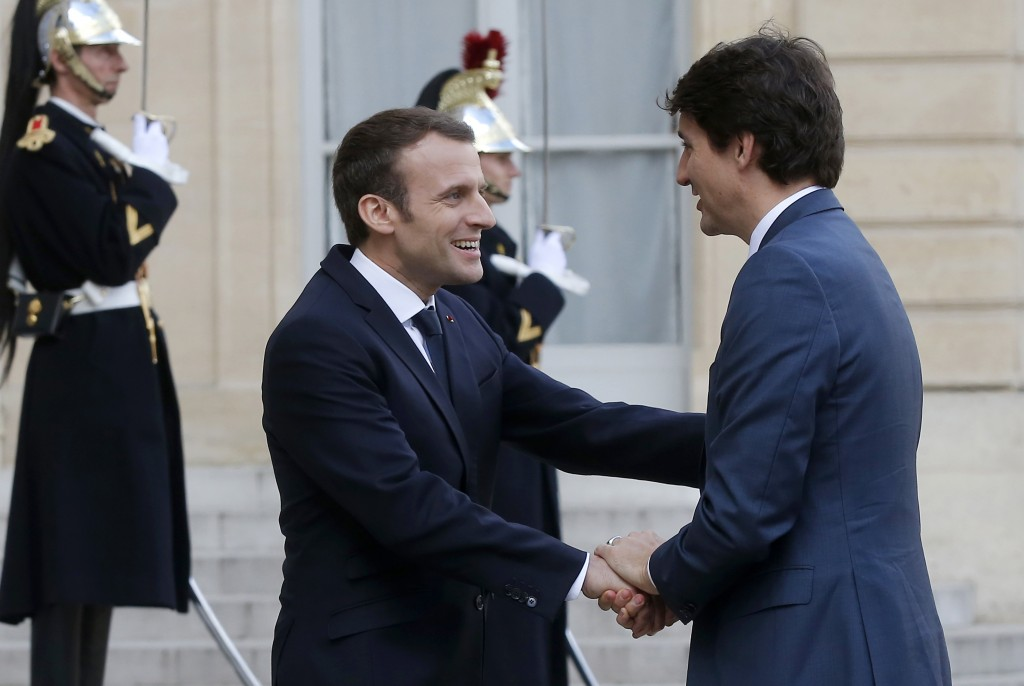 French President Emmanuel Macron, left, welcomes Canadian Prime Minister Justin Trudeau on the occasion of their meeting at the Elysee Palace in Paris