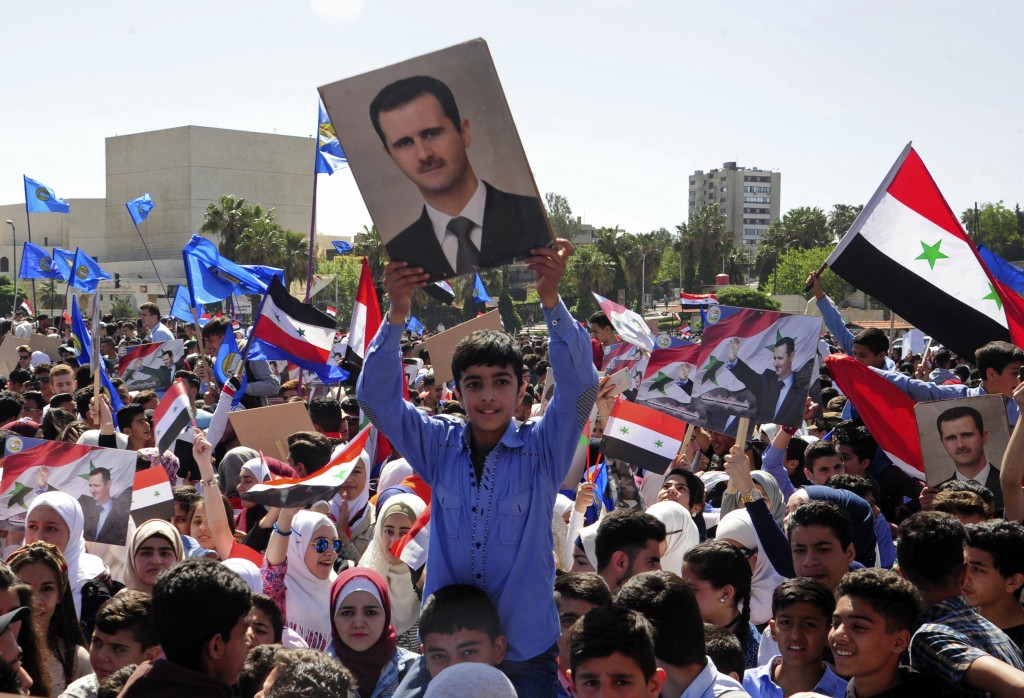 In this photo released by the Syrian official news agency SANA, protesters wave flags and portraits of President Bashar Assad, as they march during a