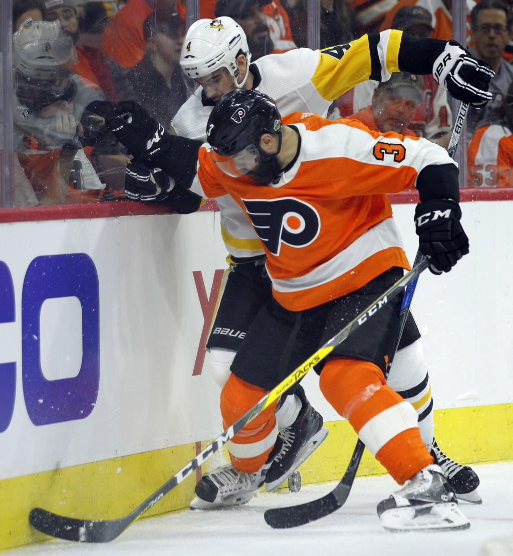 Philadelphia Flyers' Radko Gudas, front, and Pittsburgh Penguins' Justin Schultz, battle for control of the puck behind the Flyers' net during the fir