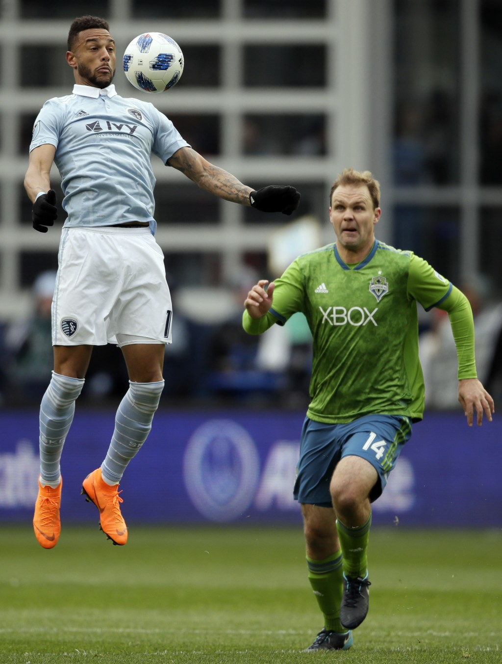 Sporting Kansas City forward Khiry Shelton, left, receives the ball while covered by Seattle Sounders defender Chad Marshall, right, during the first
