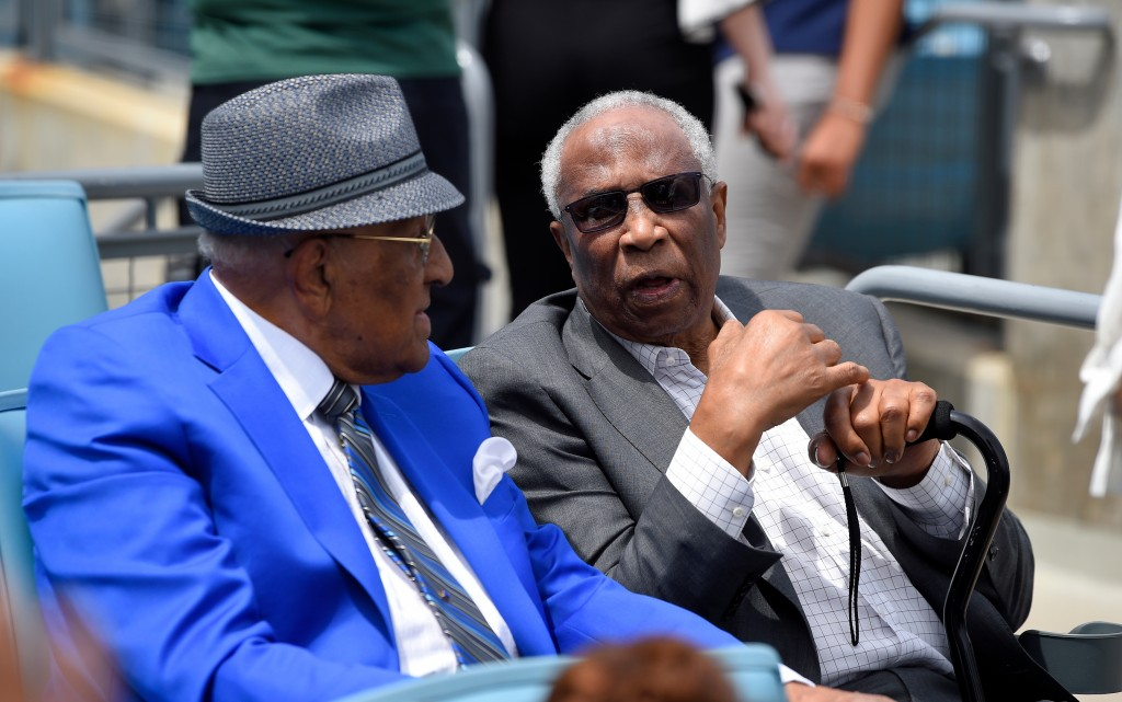 Former Dodger Don Newcombe, left, and former Orioles and Reds outfielder Frank Robinson talk prior to a baseball game between the Dodgers and the Ariz