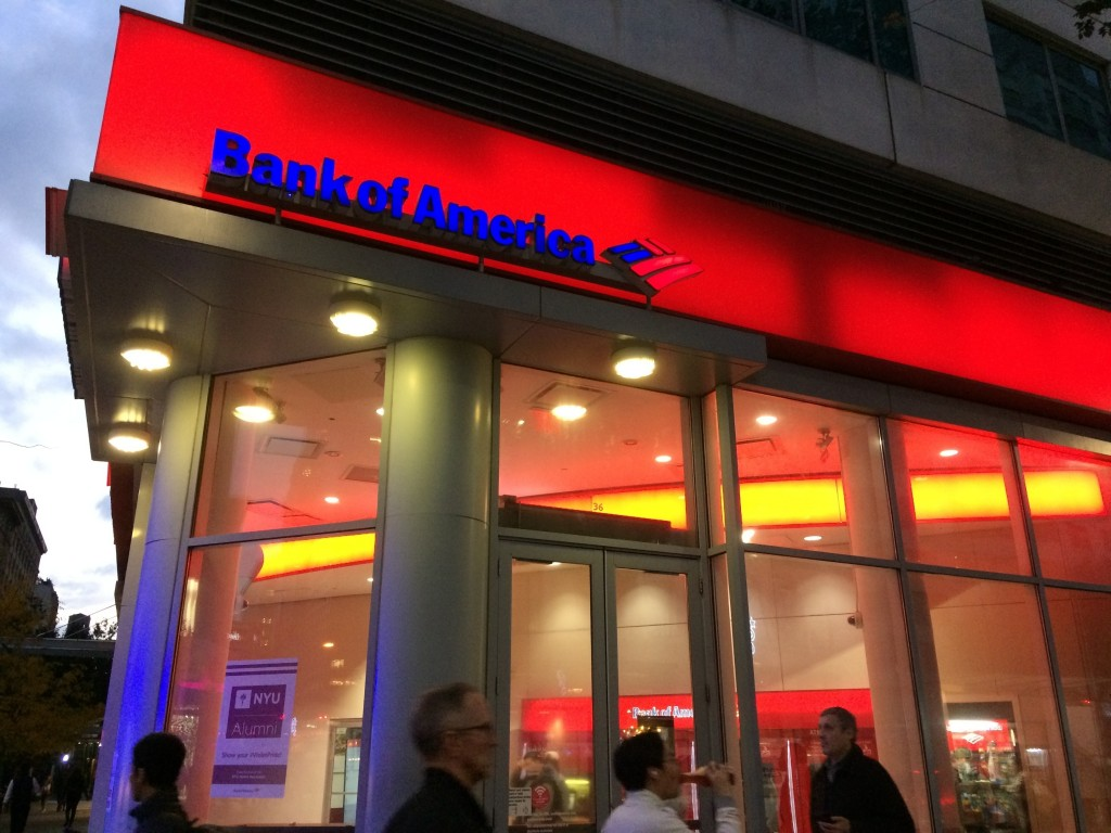 FILE- In this Nov. 6, 2017, file photo, people walk by a branch office of Bank of America in New York. Bank of America Corp. reports earnings Monday,