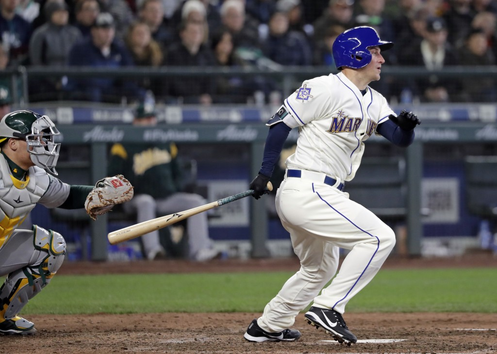 Seattle Mariners' Kyle Seager, right, grounds out to end a baseball game as Oakland Athletics catcher Bruce Maxwell looks on in the ninth inning Sunda