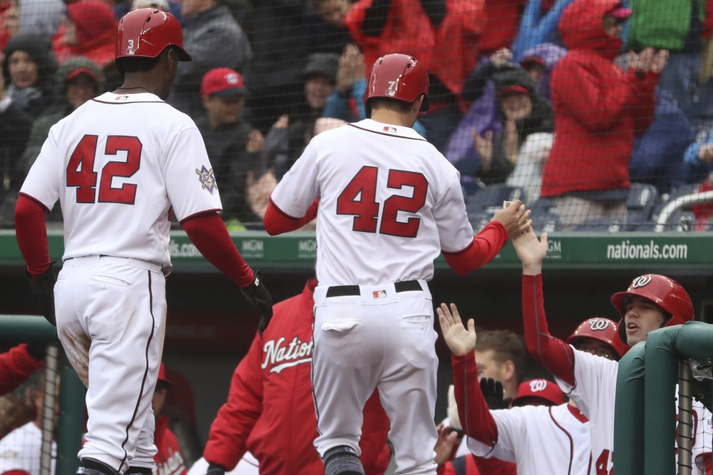 Washington Nationals' Michael Taylor, left, and Trea Turner, center, score on a passed ball during the fifth inning of a baseball game against the Col