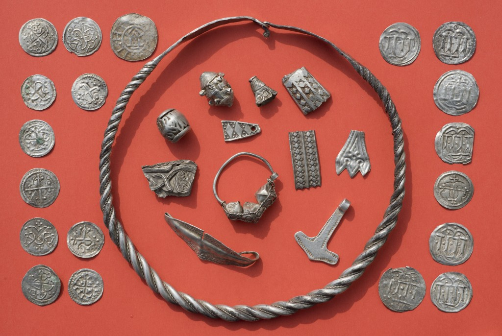 In this April 13, 2018 photo medieval jewelry and coins are displayed on a table after a medieval silver treasure had been found near Schaprode on the