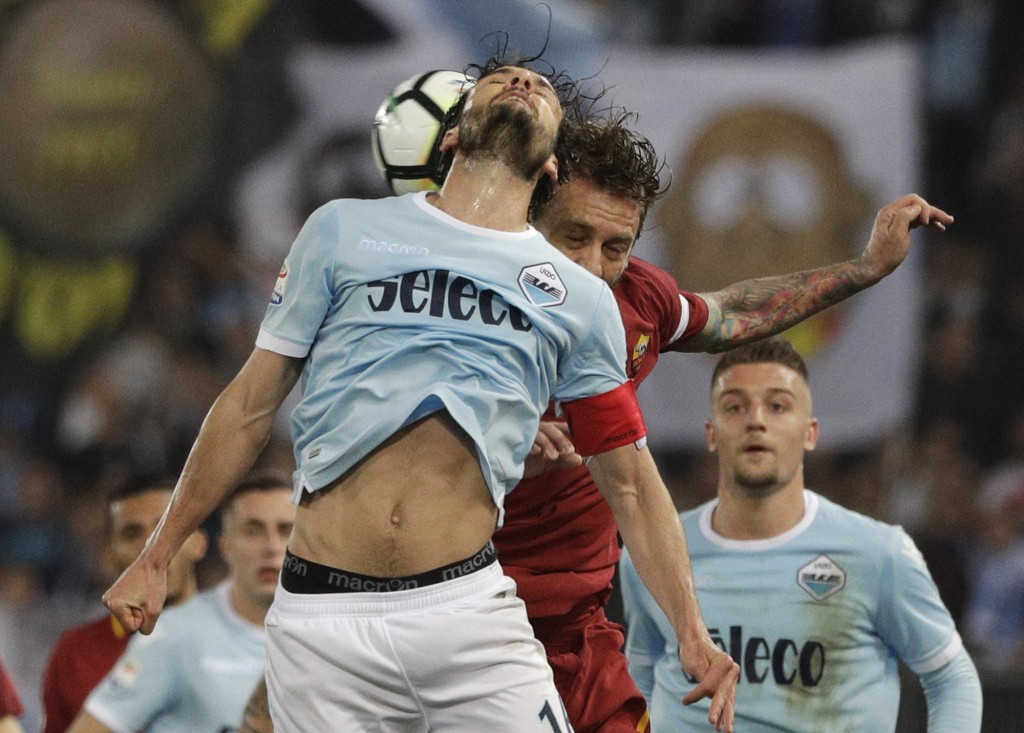Lazio's Marco Parolo, front, and Roma's Daniele De Rossi vie for the ball during an Italian Serie A soccer match between AS Roma and Lazio, at the Oly