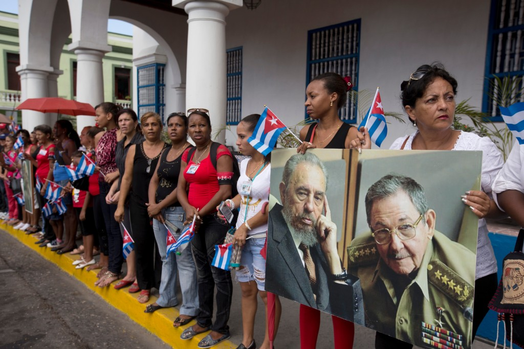 FILE - In this Dec. 3, 2016 file photo, women hold a portrait of the late Fidel Castro, and of his brother Cuba's President Raul Castro, as they wait