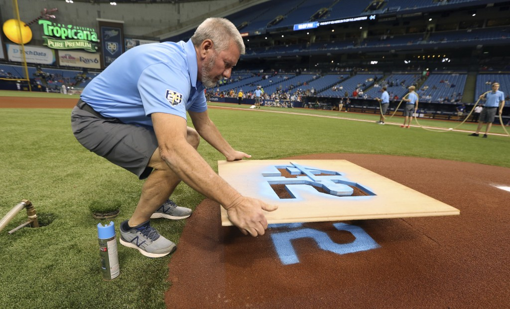 """Tampa Bay Rays head grounds crew member Dan Moeller lifts a stencil after spray painting """"42,"""" in honor of baseball great Jackie Robinson, on the back"""