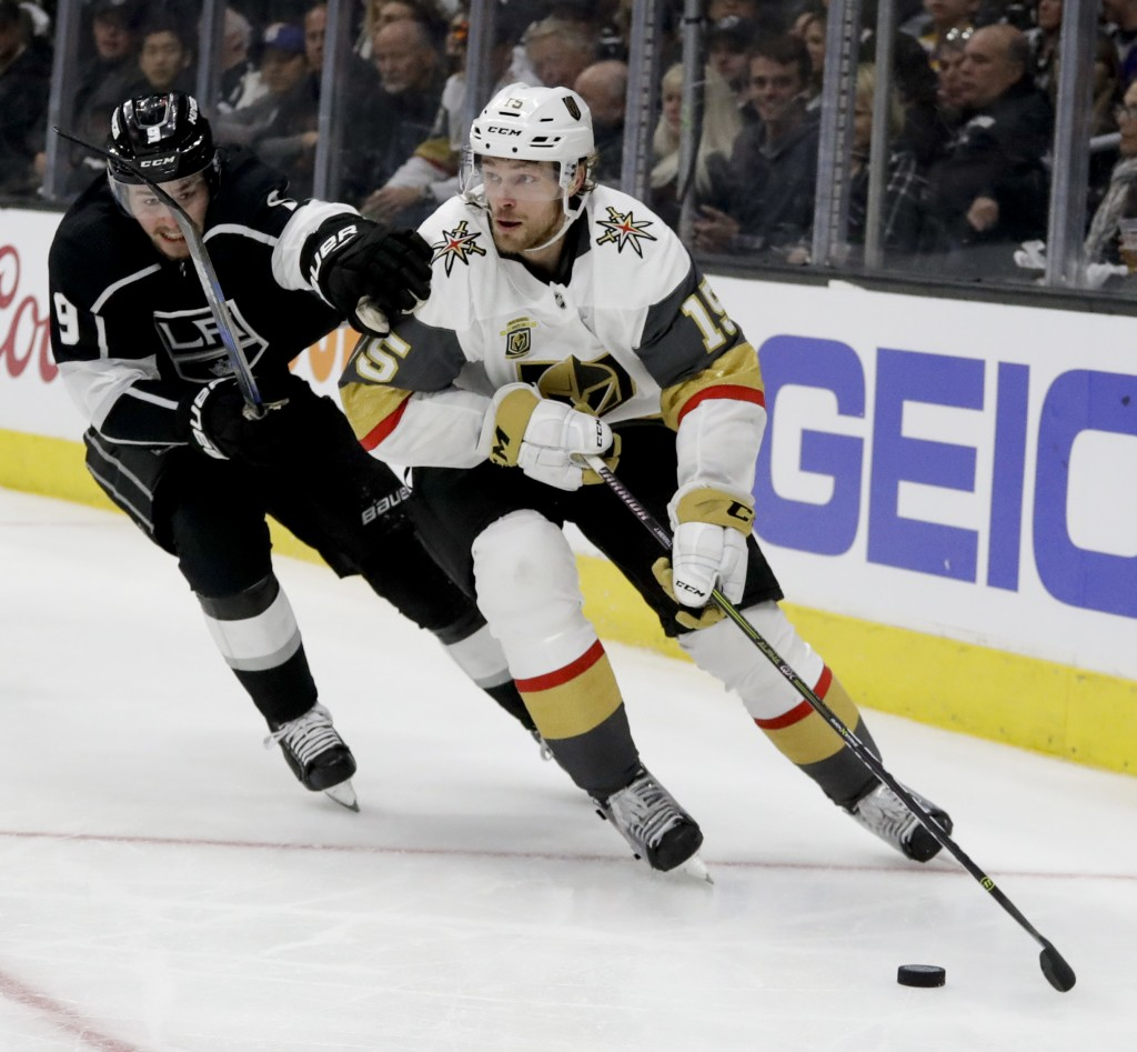 Los Angeles Kings left wing Adrian Kempe, left, battles Vegas Golden Knights defenseman Jon Merrill for the puck during the second period of Game 3 of
