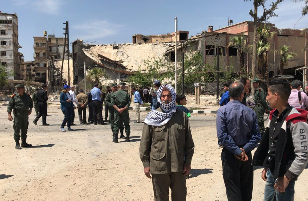 Policemen and civilians stand in front of damaged buildings in the town of Douma, the site of a suspected chemical weapons attack, near Damascus, Syri