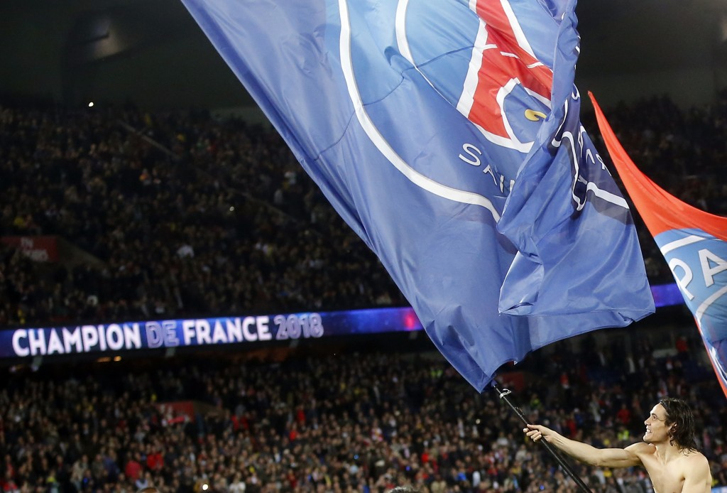 PSG's Edinson Cavani waves a PSG's flag and celebrates at the end of the French League One soccer match between Paris Saint Germain and Monaco at the