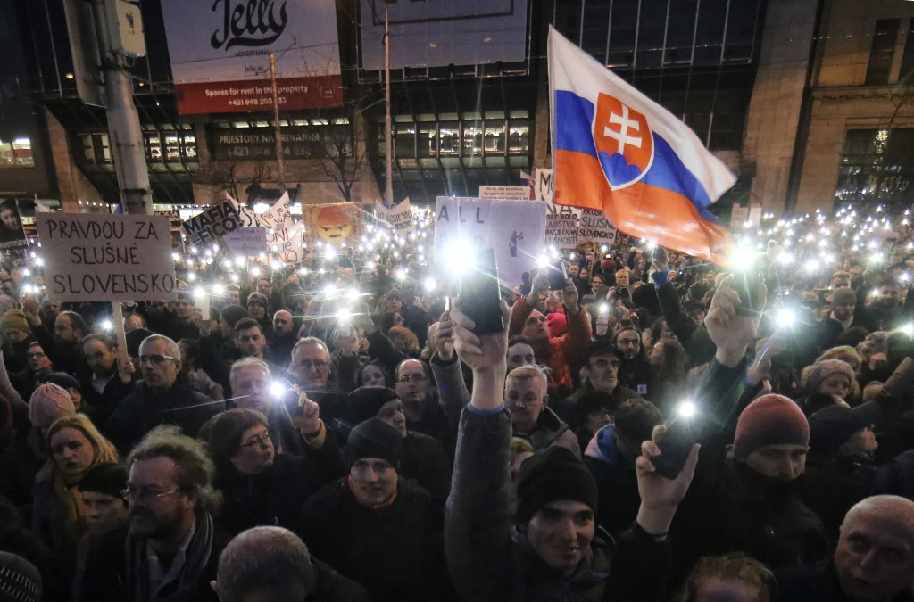FILE- In this Friday, March 9, 2018, file picture demonstrators light the torches of their smartphones during an anti-government rally in Bratislava,