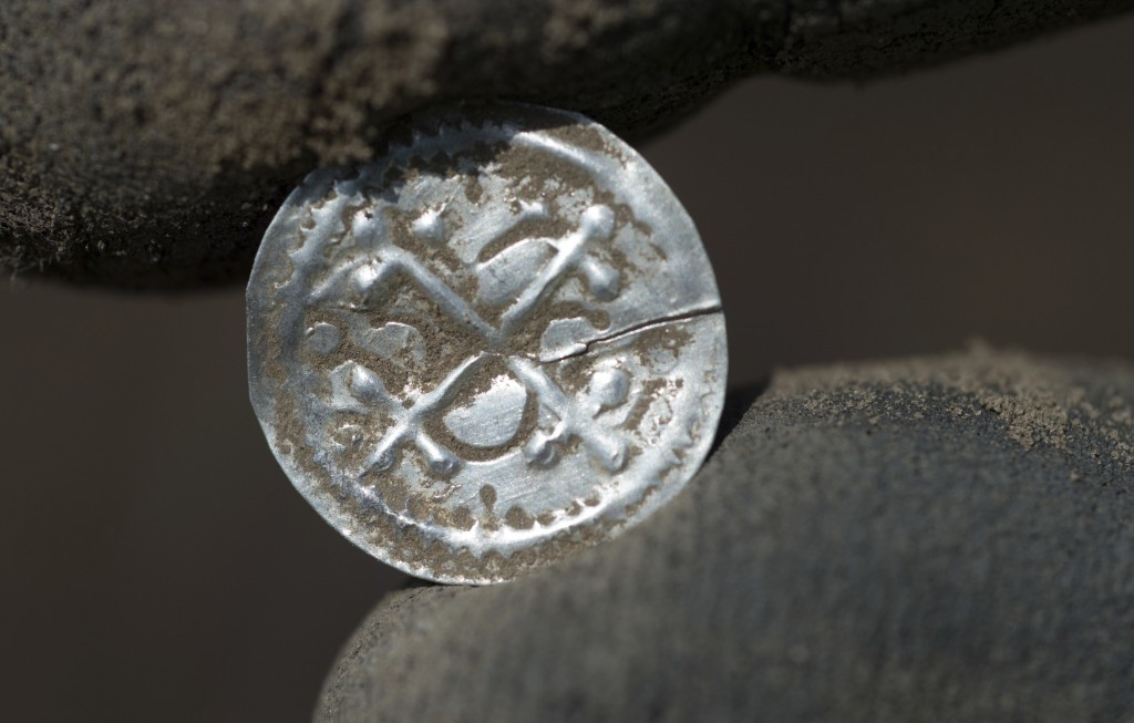 In this April 13, 2018 photo an archeologist holds an ancient Danish coin which was minted under King Harald Bluetooth after a medieval silver treasur