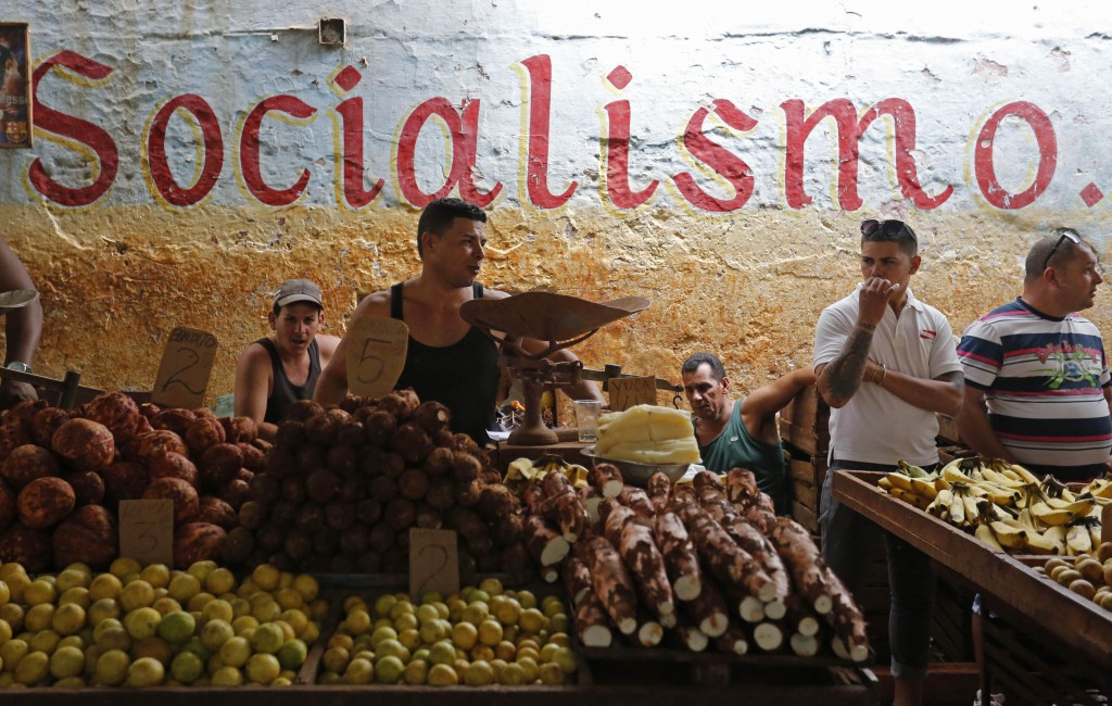 FILE - In this Dec. 20, 2014 file photo, workers stand behind their food stalls at a state-run market in Havana, Cuba. The average monthly state salar
