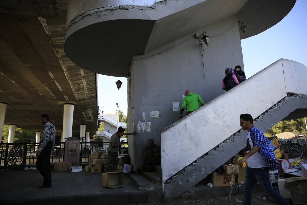 Syrians walk up stairs of a bridge in Damascus, Syria, Sunday, April 15, 2018. Syria's President Bashar Assad spoke Sunday to a group of visiting Russ