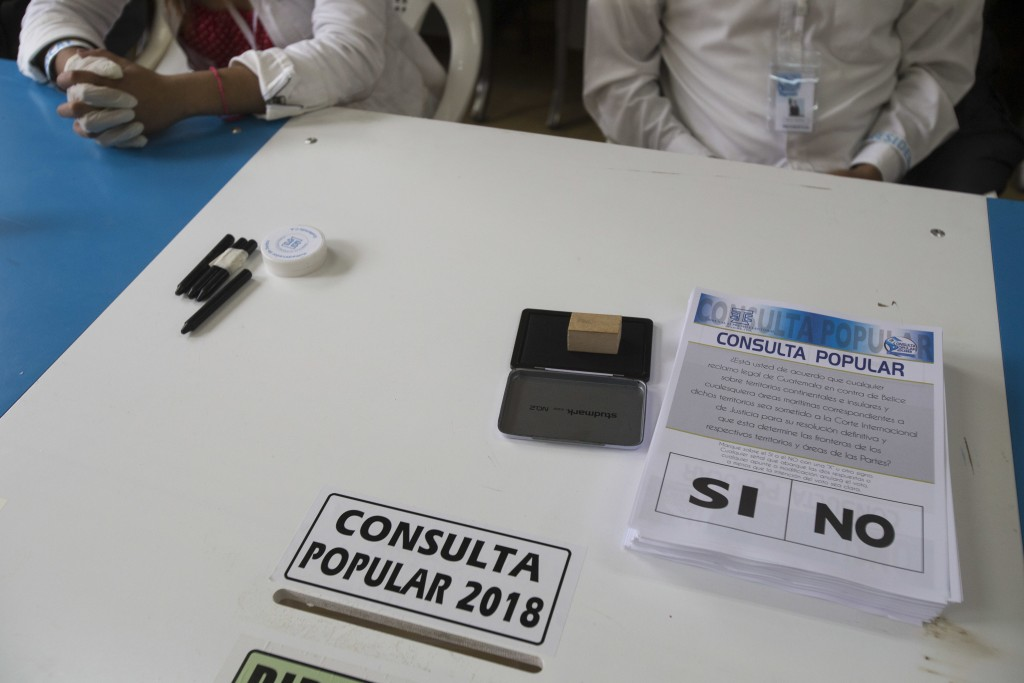 Electoral volunteers wait for voters during a plebiscite on a border dispute with Belize, in Guatemala City, Sunday, April 15, 2018. Guatemalans are d