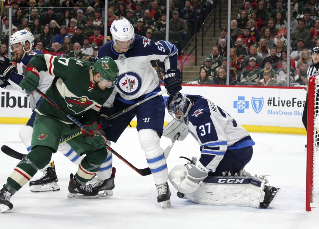 Minnesota Wild left wing Marcus Foligno (17) is stopped by Winnipeg Jets goalie Connor Hellebuyck (37) with defensive help from Jets' defenseman Tyler