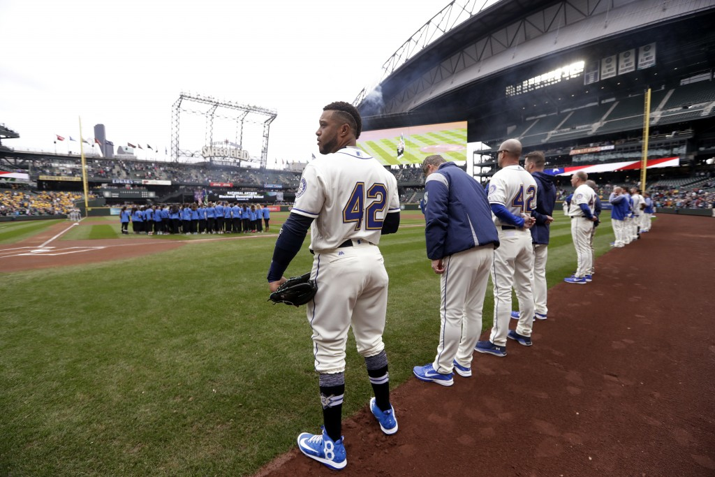 Seattle Mariners' Robinson Cano, left, wears a No. 42 on his back, along with the rest of the team and the Oakland Athletics, as he stands before a ba