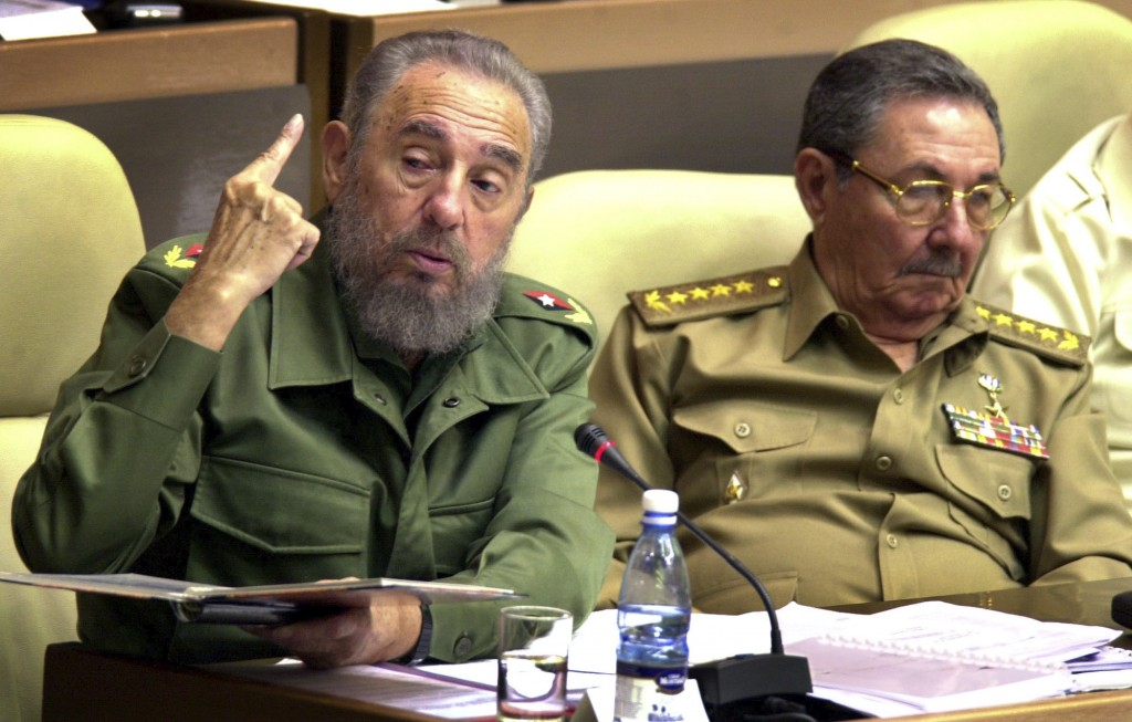 FILE - In this Nov. 2, 2002 file photo, Cuban President Fidel Castro, left, seated next to his brother Defense Minister Raul Castro and first Vice Pre