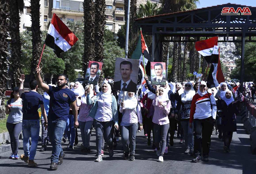 In this photo released by the Syrian official news agency SANA, Syrian protesters hold their national flags and portraits of their president Bashar As