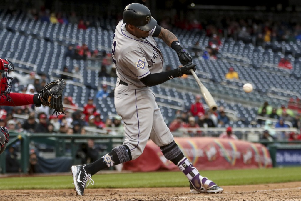 Colorado Rockies' Ian Desmond hits a home run to put the Rockies ahead in the ninth inning against the Washington Nationals at Nationals Park Sunday,