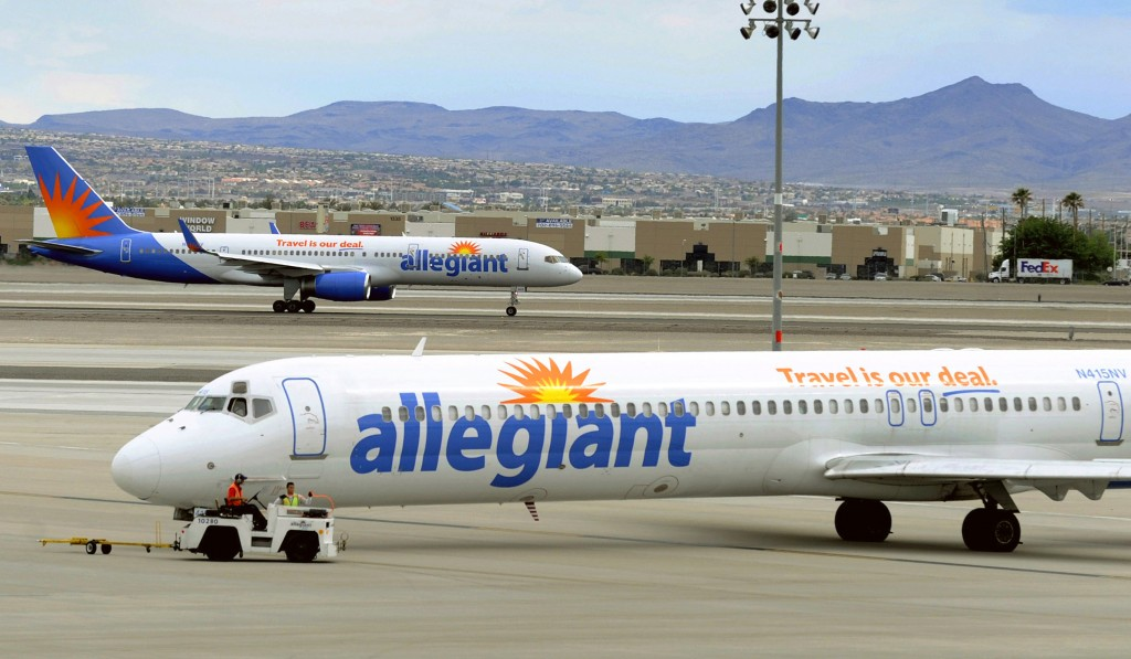 File - In this May 9, 2013, file photo, two Allegiant Air jets taxi at McCarran International Airport in Las Vegas. Shares of Allegiant Air's parent c