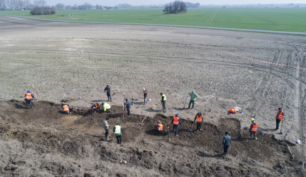 In this April 13, 2018 photo archaeologists search for coins and jewelry after a medieval silver treasure had been found near Schaprode on the norther