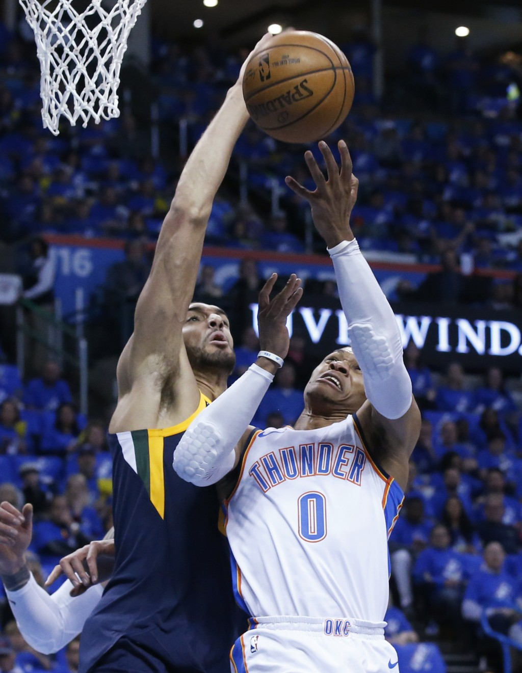 Utah Jazz center Rudy Gobert, left, blocks a shot by Oklahoma City Thunder guard Russell Westbrook (0) in the first half of Game 1 of an NBA basketbal