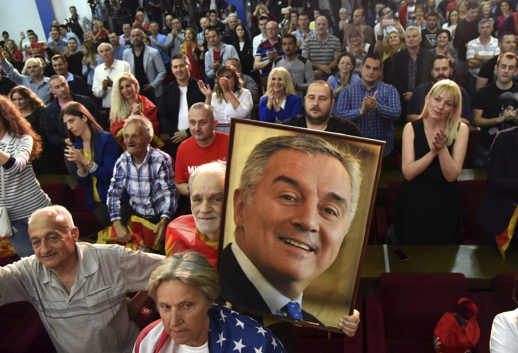 A supporter of Montenegro's former prime minister and long-ruling Democratic Party of Socialists leader Milo Djukanovic holds his picture during a cel