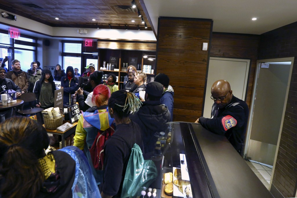 A plain-clothed police officer, right, mans a position behind the counter at the Starbucks that has become the center of protests Monday, April 16, 20