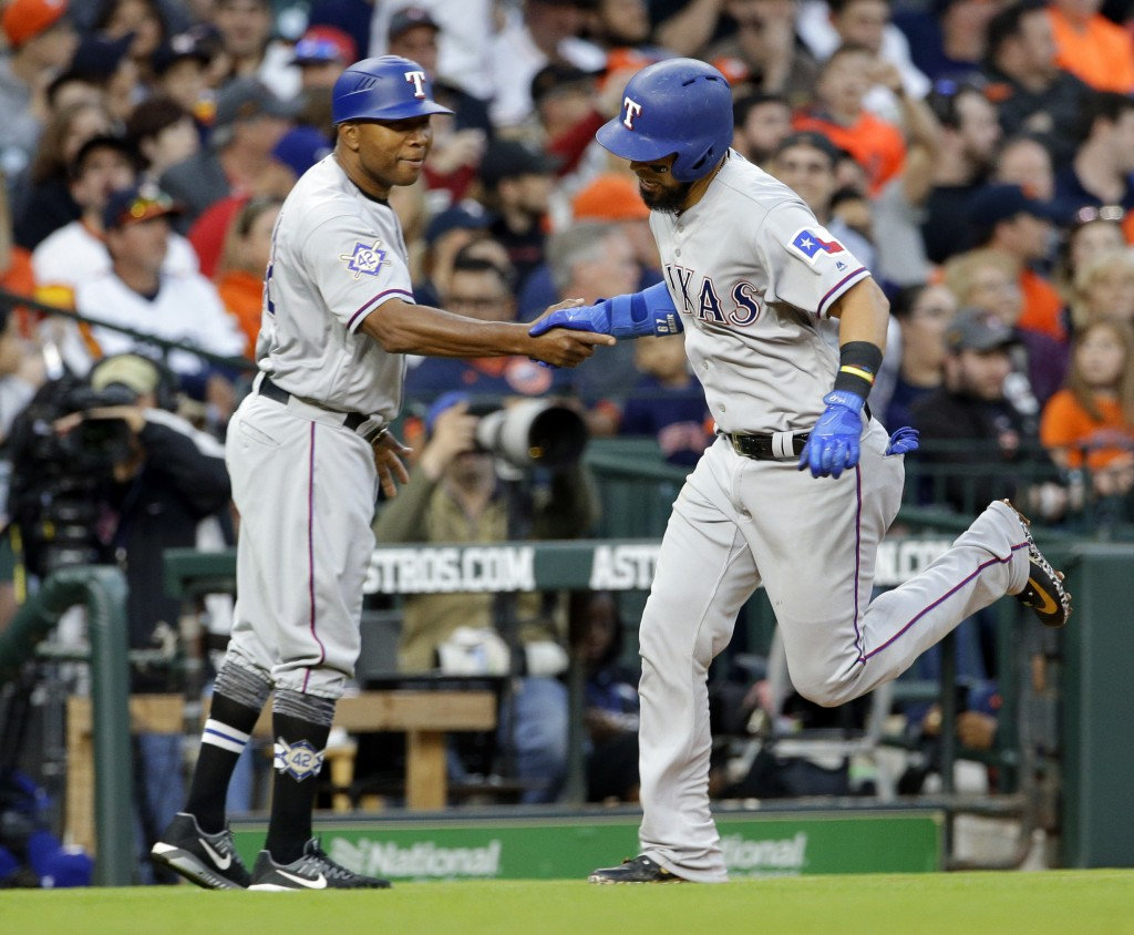 Texas Rangers third base coach Steve Buechele, left, shakes hand with Robinson Chirinos after hitting a home run during the third inning of a baseball