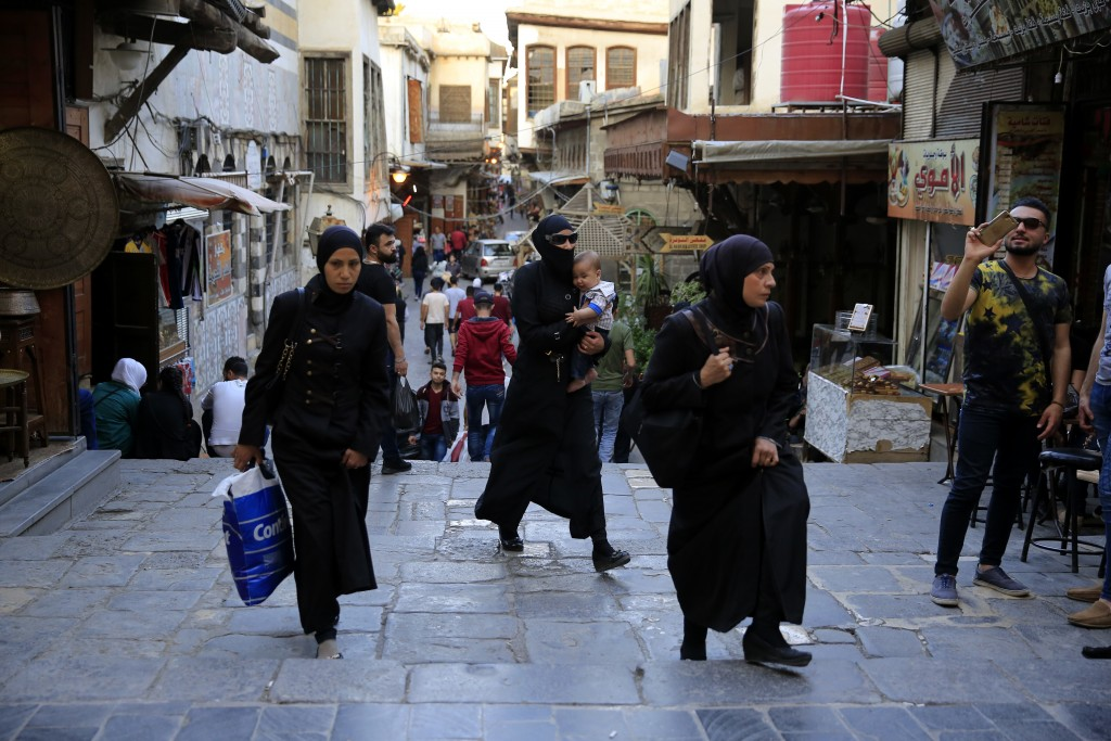 Syrians walk in the Hamidiyeh Market, in the Old City of Damascus, Syria, Sunday, April 15, 2018. Syria's President Bashar Assad spoke Sunday to a gro