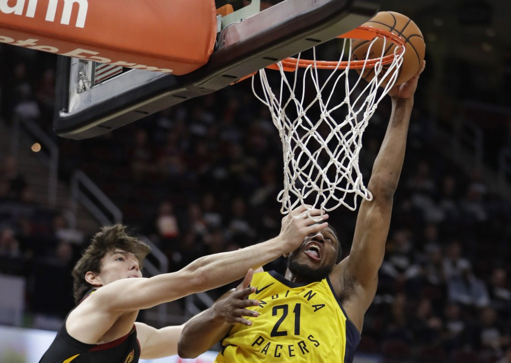 Indiana Pacers' Thaddeus Young, right, drives to the basket against Cleveland Cavaliers' Cedi Osman, from Turkey, in the second half of Game 1 of an N
