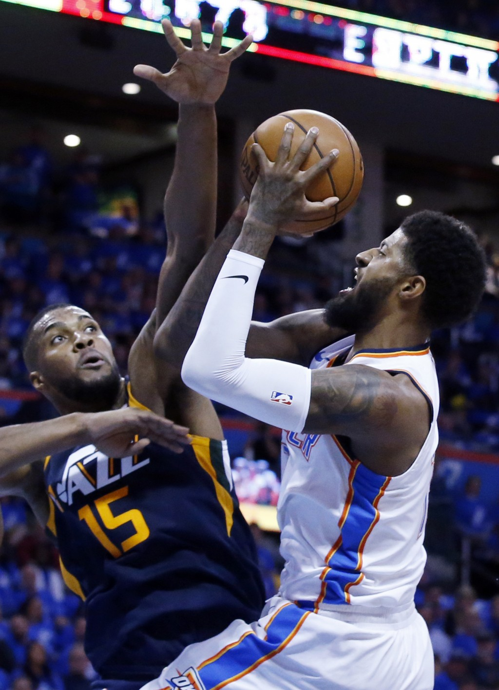 Oklahoma City Thunder forward Paul George, right, shoots as Utah Jazz forward Derrick Favors (15) defends in the first half of Game 1 of an NBA basket