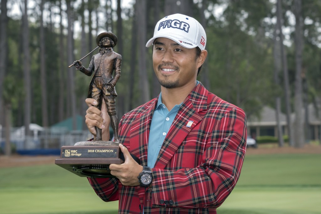 Satoshi Kodaira, of Japan, holds the trophy after winning the RBC Heritage golf tournament in a three-hole playoff against Si Woo Kim, of South Korea,